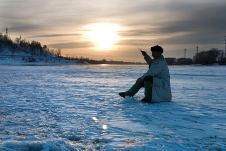 frozen lake: The fisherman on winter fishing