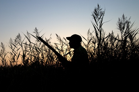 Silhouette of the hunter on a background of a morning dawn photo
