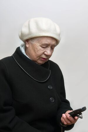 The elderly woman with mobile phone photo