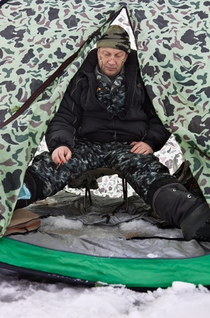 fisherman in a tent on winter fishing photo