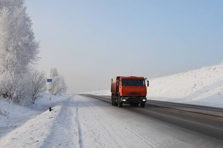 Red dump truck on winter road photo