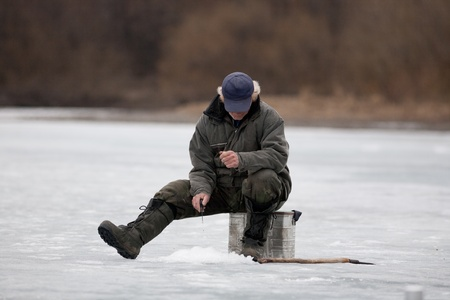 The fisherman on winter fishing fishes Stock Photo - 13093987