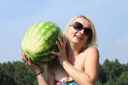 The smiling woman with the big watermelon on a background of the sky photo