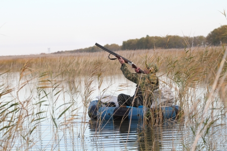 Hunter in an inflatable boat shoots duck photo