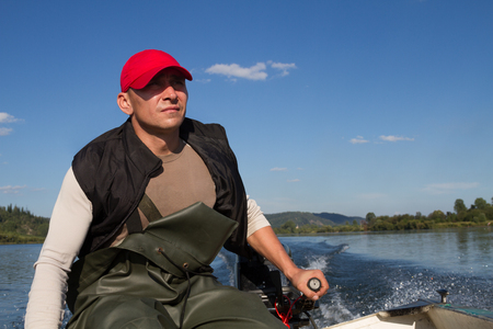 steers: man steers the boat with outboard motor