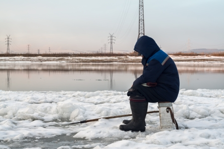The fisherman on winter fishing fishes photo