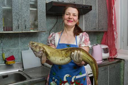 burbot: mujer en la cocina con el gran pez Foto de archivo