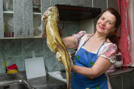 lota: mujer en la cocina con el gran pez Foto de archivo