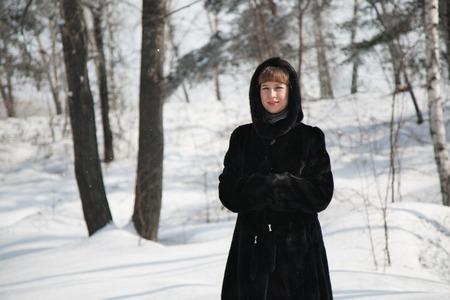 manteau de fourrure: fille dans la for�t d'hiver dans un manteau de fourrure noire