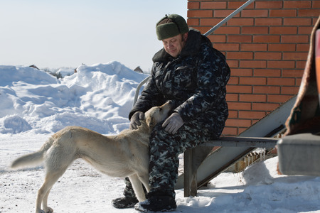 wintery day: A man in camouflage clothing stroking dog