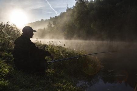 Fishing pole: fisherman with a fishing pole at sunrise on the lake