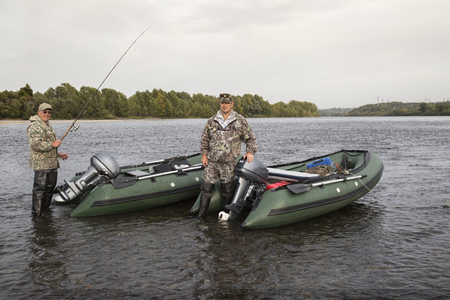 motor boats: Two fisherman on the river with motor boats