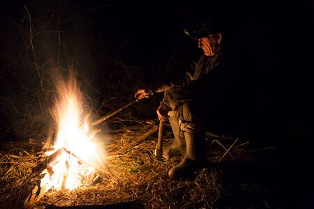man sitting around the campfire at night photo
