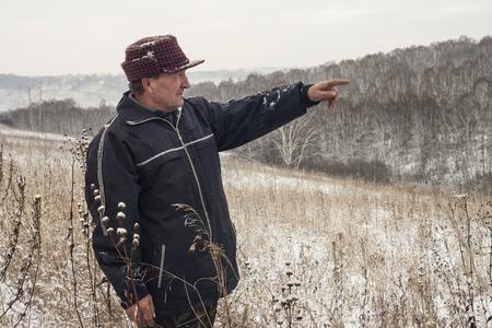 elderly man shows a hand afar photo