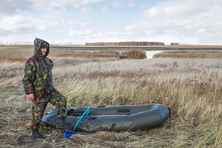 Hunter pumps up an inflatable boat photo
