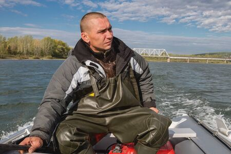 outboard: man steers the boat with outboard motor