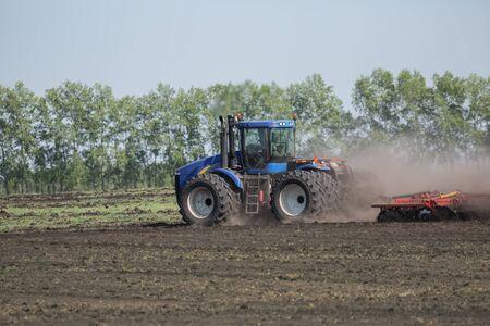 arando: tractor con arado de arar un campo Foto de archivo