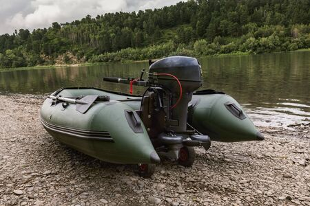 green boat: the green boat of pvc with the water-jet engine on the river bank Stock Photo