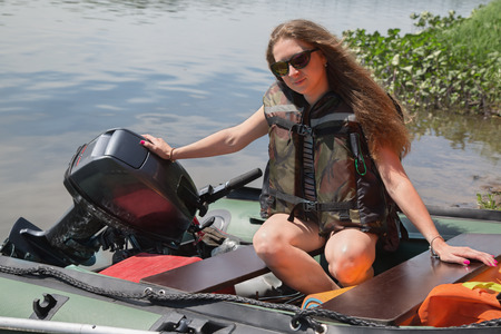 life jacket: girl in a life jacket sits in a boat with outboard motor