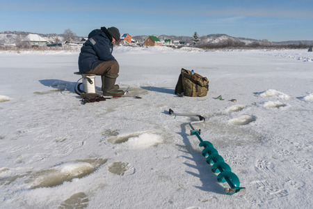 Winter fisherman on the river ice photo