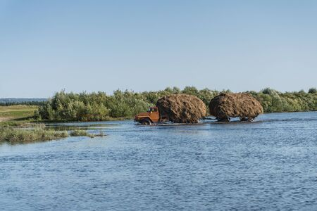 A truck with a trailer carries hay through the river Stock Photo