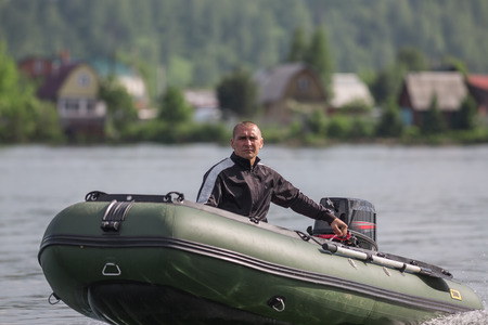 A man is riding in a green boat with outboard motor