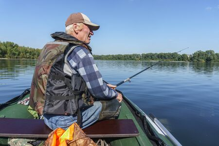 fisherman sitting in the boat fishing spinning   Stock Photo