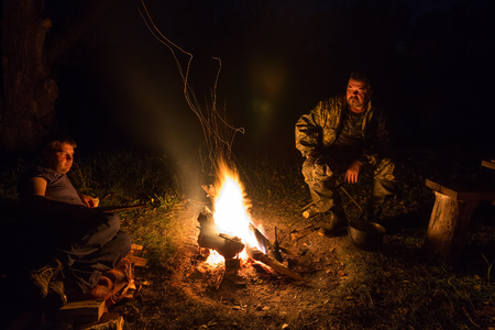 Two men are sitting by the campfire