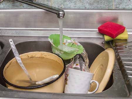 dirty dishes in a sink under running water