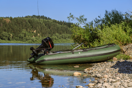 the green boat of pvc with the water-jet engine on the river bank Stock Photo