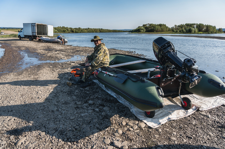 the fisherman sits in a boat with a motor on the river bank Stock Photo