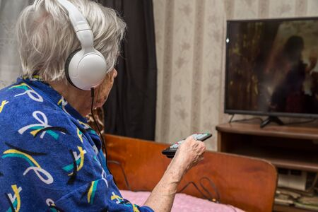 A very old woman with headphones is watching TV Stok Fotoğraf