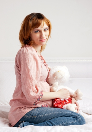 The smiling beautiful pregnant woman with a plush toy photo