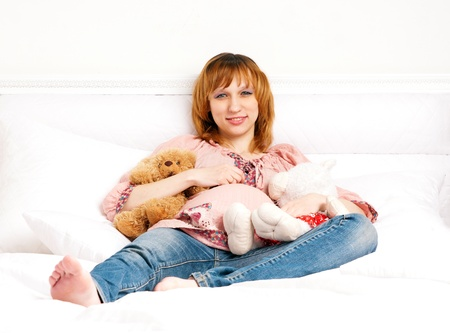 The smiling pregnant young woman on a bed with plush toys photo