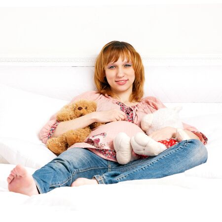 pregnant jeans: The smiling pregnant young woman on a bed with plush toys