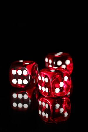 Three red dice on a black background