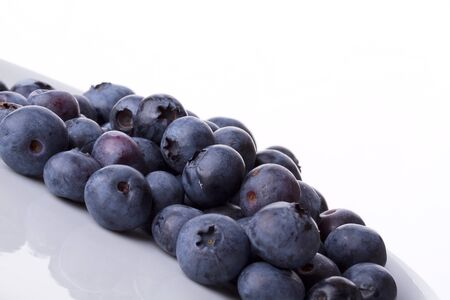 Blueberry on a white plate agains a white background