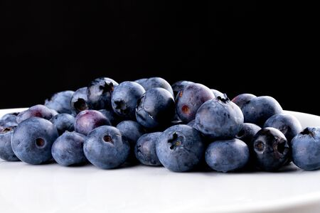 Blueberry on a white plate agains a black background