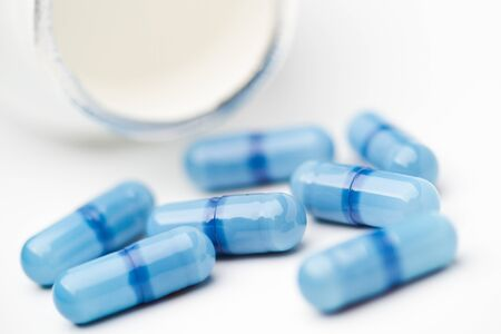Blue capsules in front of a white pill bottle