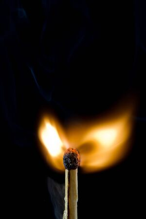 Closeup of match just ignited against black background photo