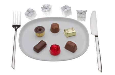 Chocolate pralines on a plate with small presents around photo