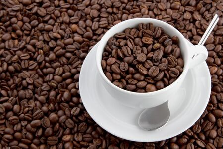 Cup of coffee beans on a layer of coffee beans Stock Photo - 13130318