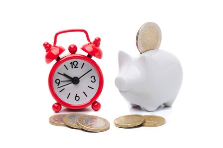 Alarm clock and piggy bank with coins Stock Photo