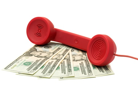 Red phone handset on a fan of banknotes