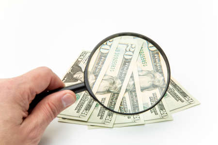 hand holding magnifying glass, looking at banknotes