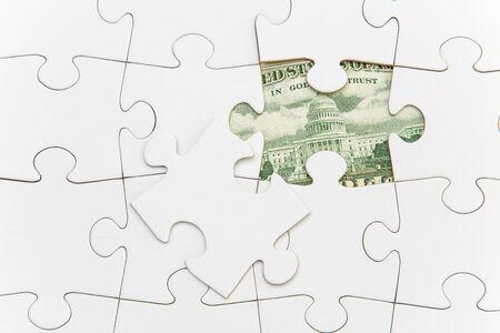 Banknote hidden behind puzzle piece