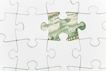 Jigsaw atop of banknote Stock Photo