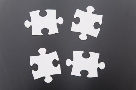 Four jigsaw pieces on a black surface