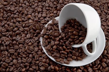 Cup filled with coffe beans on a layer of beans