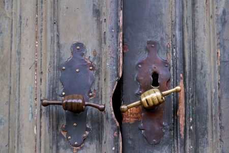 Old rustic door with closeup of hand shaped handles  Stock Photo